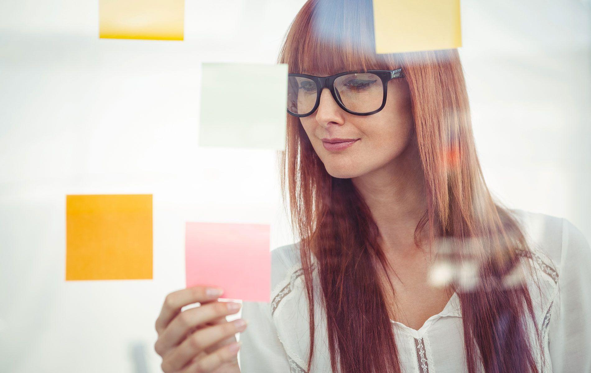 Eine Frau gruppiert ihre Inhalte mithilfe von bunten Post-Its.